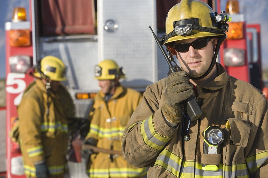 A firefighter talks over a radio to colleagues.