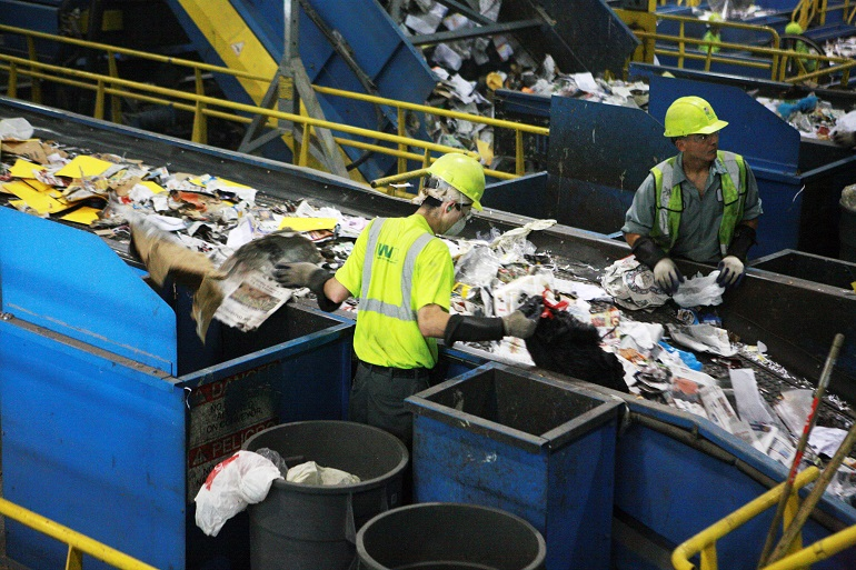 Two men work in a recycling facility